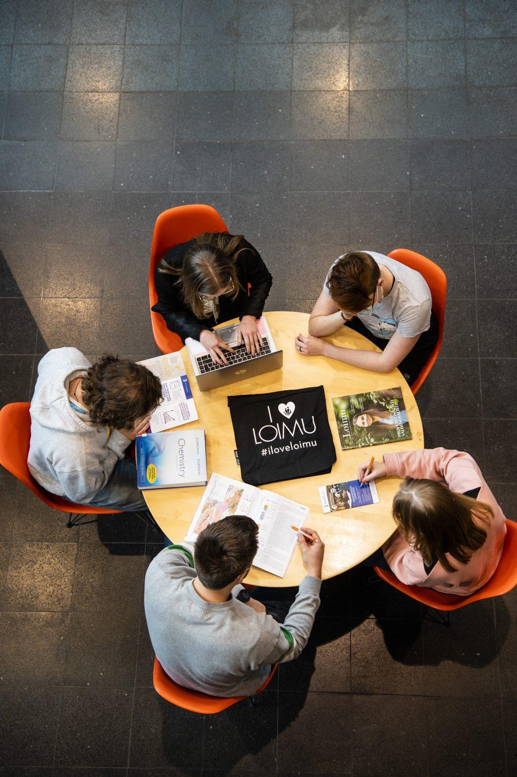 Opiskelijoita pöydän ääressä