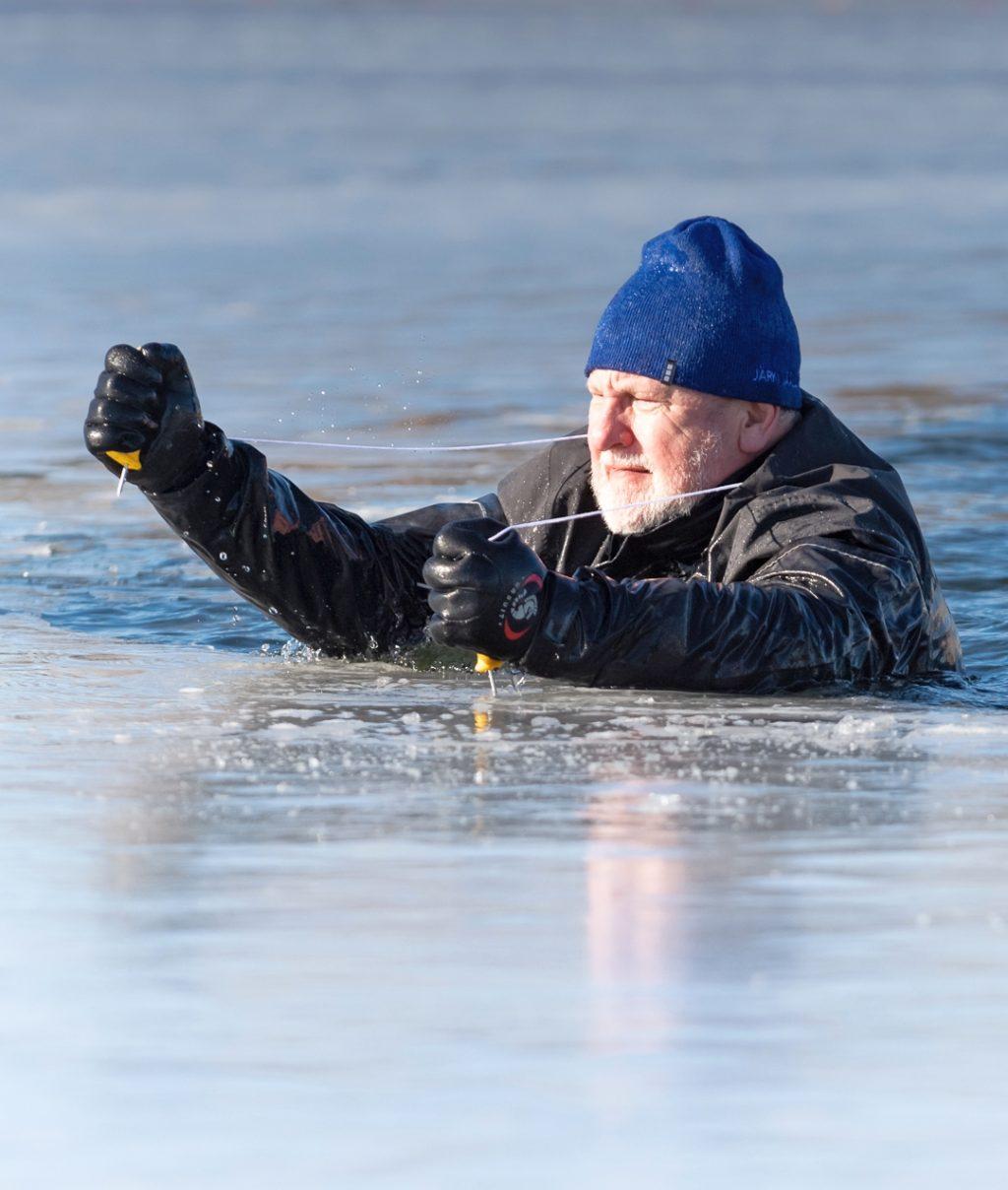Loimun puheenjohtaja Jouni Vainio pelastautuu avannosta jäänaskalien avulla.